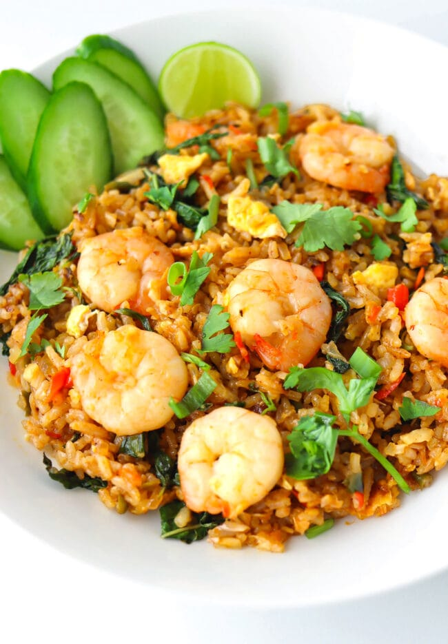 Front view of plate with spicy prawn fried rice with cucumber slices and a lime wedge.