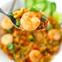"Spoon holding up a bite of spicy fried rice and a prawn. Text overlay ""Thai Roasted Chili Fried Rice with Prawns"" and ""thatspicychick.com""."