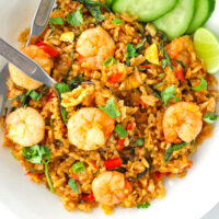 "Spicy prawn fried rice on a plate with a fork and spoon. Text overlay ""Thai Roasted Chili Fried Rice with Prawns"" and ""thatspicychick.com""."