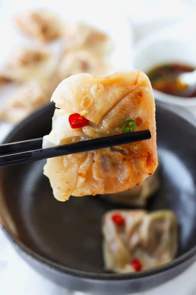 Chopsticks holding up a wonton to show the crispy pan-fried bottom.