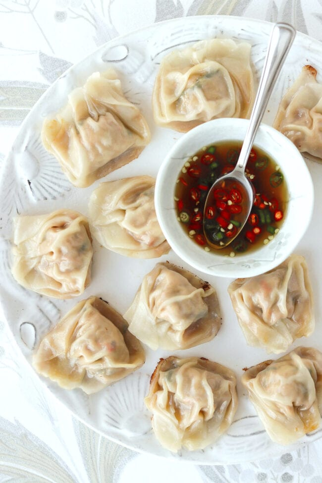 Top view of pan-fried spicy Thai basil wontons and prik nam pla in a bowl with a spoon on a plate.