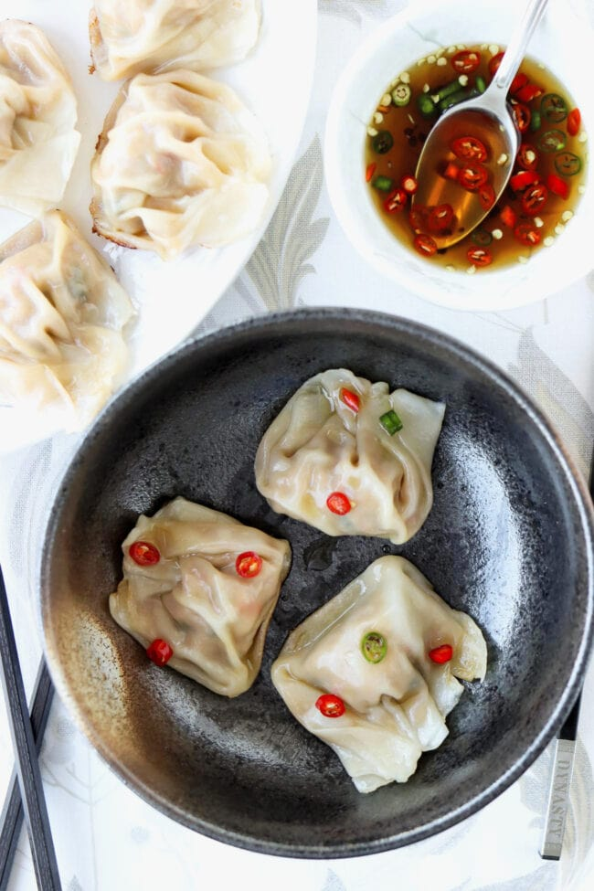 Top view of plate and bowl with three spicy thai basil wontons topped with fish sauce and chopped chilies.