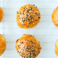 "Top view of baked bagel bombs on parchment paper. Text overlay ""Easy Homemade Stuffed Bagel Bombs"" and ""thatspicychick.com""."