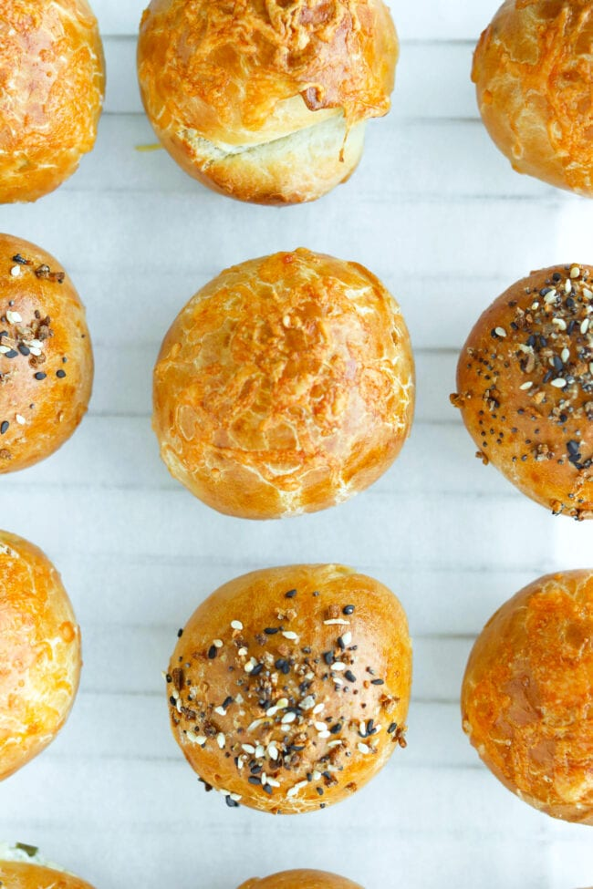 Close-up top view of stuffed baked bagel bombs lined up on nonstick cooking paper.