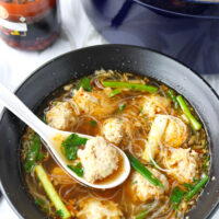 "Front view of spoon with a meatball and soup in bowl of noodle soup. Text overlay ""Thai Glass Noodle Soup with Chicken & Prawn Meatballs"" and ""thatspicychick.com""."