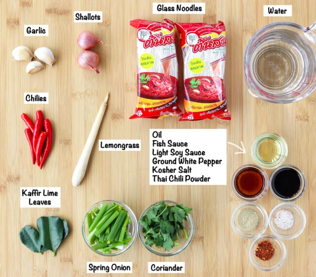 Labeled ingredients for Thai glass noodle soup on a wooden board.