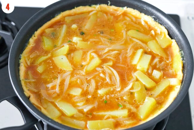 Beaten egg with potatoes and onion cooking in skillet on stovetop.