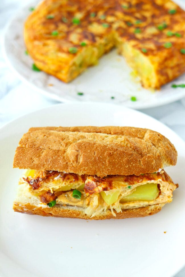 Omelette baguette sandwich on a plate. Plate with Tortilla Español with a wedge cut out behind.