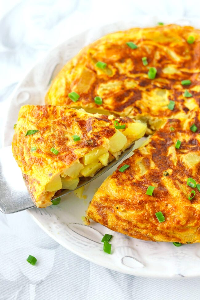 Front view of Spanish omelette on a plate with a wedge on a cake server.