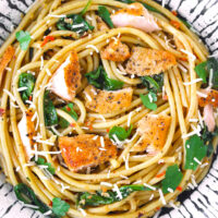 Close-up top view of salmon pasta with baby spinach and grated cheese in a plate.