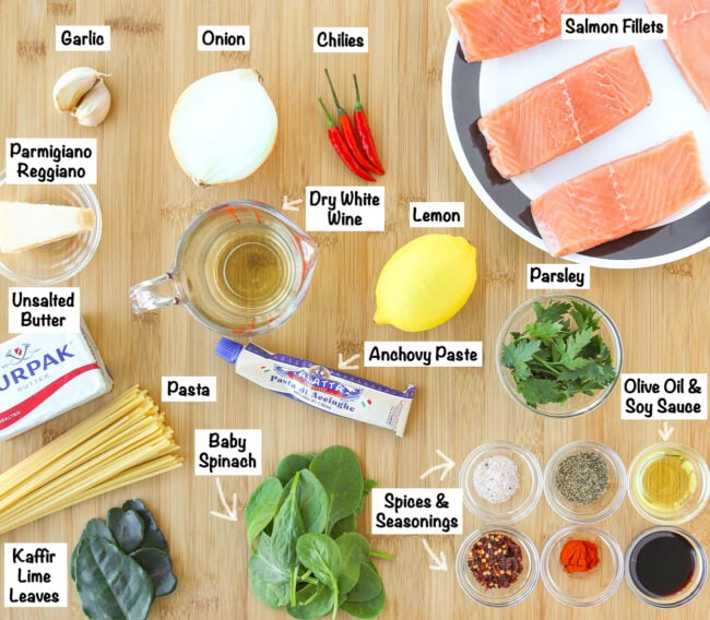 Labeled ingredients for Salmon Pasta with Anchovy-Garlic Sauce on a wooden board.
