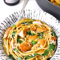 """Front view of salmon pasta with a fork on a plate. Text overlay """"Salmon Pasta with Anchovy-Garlic Sauce"""" and """"thatspicychick.com""""."""