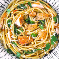 Top view of salmon pasta with baby spinach, parsley, and grated cheese in a plate.