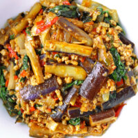 """Close-up top view of a serving bowl with an eggplant stir-fry dish. Text overlay """"Thai Eggplant Stir-fry with Thai Chili Paste, Pork & Basil"""" and """"thatspicychick.com""""."""