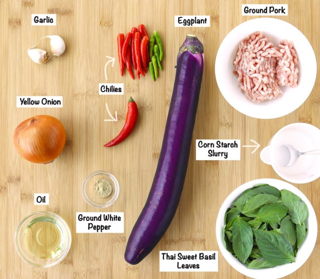 Labeled fresh and pantry ingredients for Thai Eggplant Stir-fry on a wooden board.