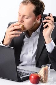Hardworking man eating at his desk