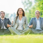 Three business people sitting in lotus position outdoors