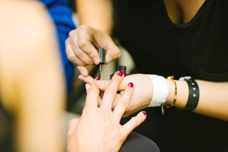 Nail salon worker painting someone else's nails.