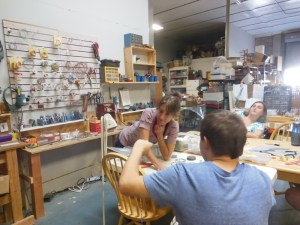 Maryanne LaRoche at Seeds for Autism works with a student in her warehouse which has many projects going simultaneously