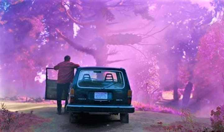 man next to car looking at pink alien landscape