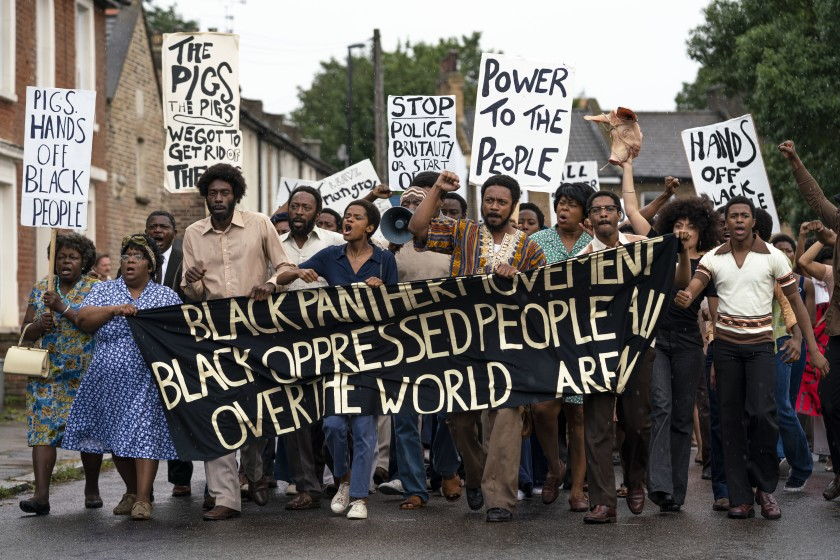 "still from the movie ""Mangrove"": a group of black protesters march holding a banner that reads ""black panther movement black oppressed people all over the world"""