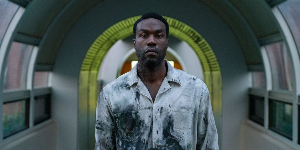"""Yahya Abdul-Mateen II as Anthony McCoy wearing stained coveralls and standing in a long circular hallway in """"Candyman"""""""
