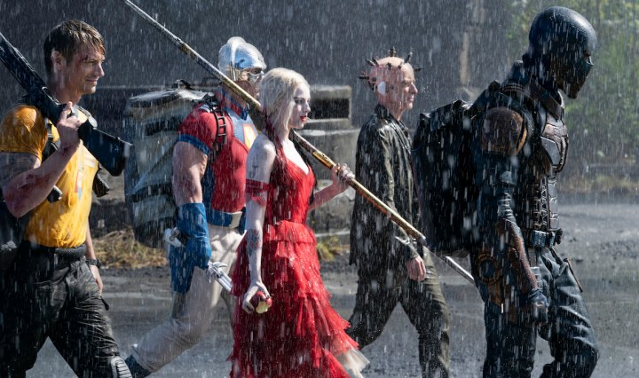 Rick Flag, Peacemaker, Harley Quinn, Thinker, and Bloodsport walk together in the rain