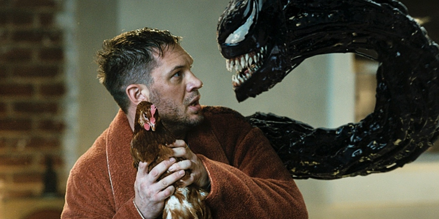 Tom Hardy as Eddie Brock holding a chicken and talking to Venom in 'Venom: Let There Be Carnage'