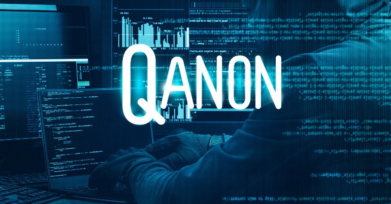 A photo of a person typing at their computer with the text QAnon overlaid on the image.