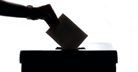 A photo of hand putting a ballot into a ballot box, ahead of the Dublin Bay South by-election in which Justin Barrett and Dolores Cahill are running as election candidates.