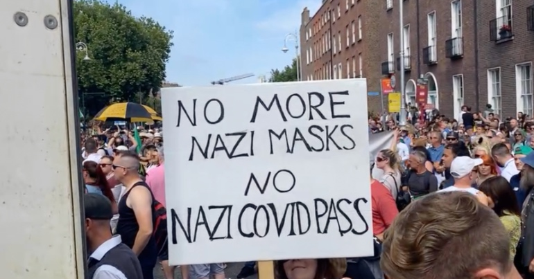 """A photo of a person at the anti-mask rally in Dublin holding a placard which reads """"No more Nazi masks. No Nazi COVID pass""""."""
