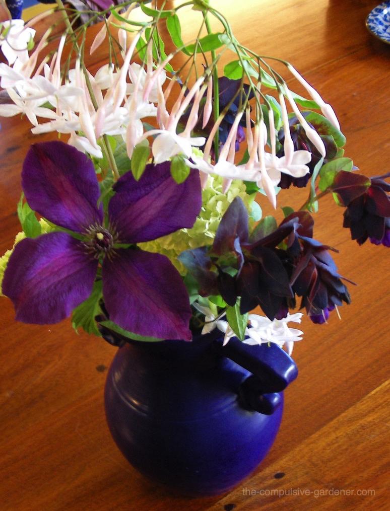 Garden floral bouquet with purple clematis and jasmine