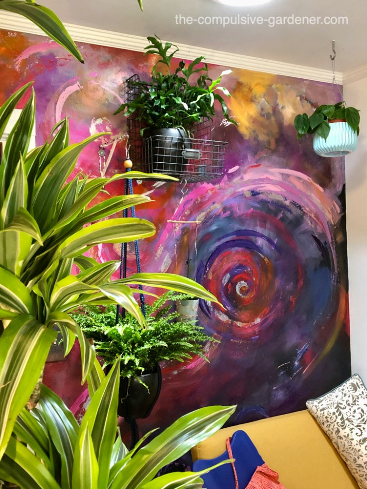 """Kangaroo paw fern, dracaena fragrans, Boston fern, heart leaf philodendron. I wanted some invigorating color in the office so I painted a cosmic swirl """"mural""""."""