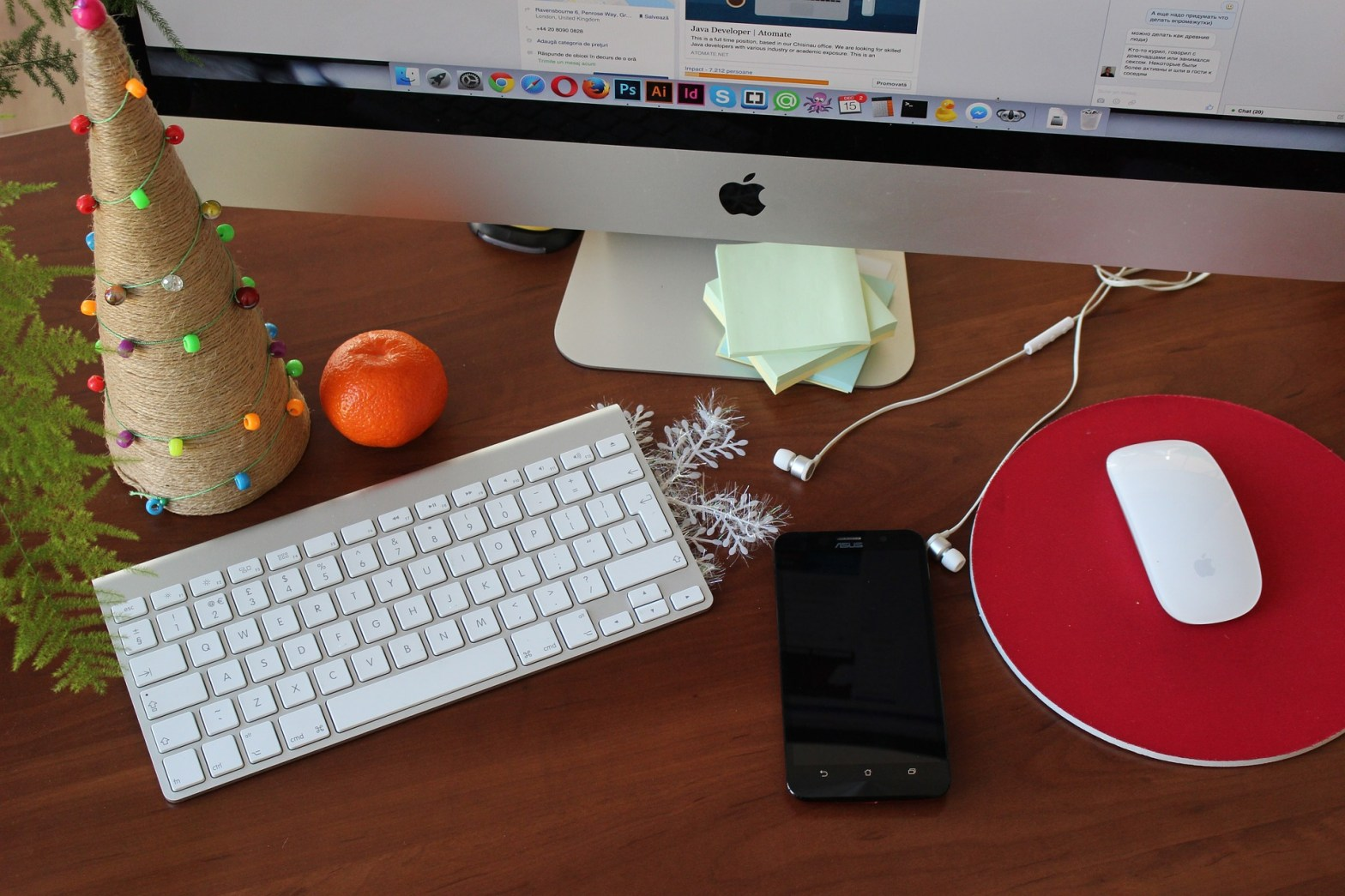 photo of a computer monitor, keyboard and mouse, surrounded by holiday decorations