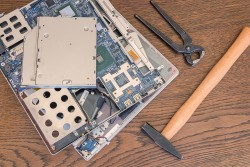 Bad computer repair, broken old computer or laptop with hammer and pliers.