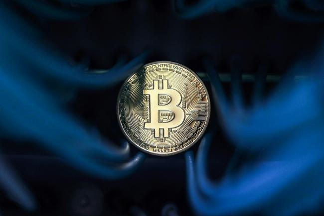 © Bloomberg. A bitcoin sits among an Ethernet cables inside a communications room at an office in this arranged photograph in London, U.K. Photographer: Chris Ratcliffe/Bloomberg