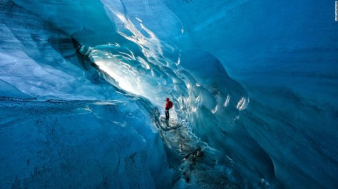 """Photo: Tom Schifanella, USA: """"Since 2000, Icelandic glaciers have lost 12% of their size, in less than 15 years. Pictured here, Icelandic guide Hanna Pétursdóttir admires an ice cave inside the Svínafellsjökull Glacier, which she notes is rapidly expanding due to the effects of global warming,"""" wrote Schifanella."""