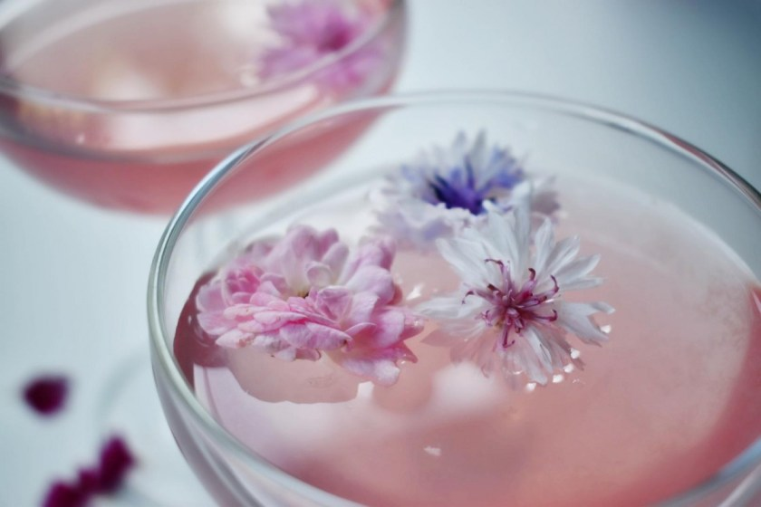 The Lemon Hibiscus Twist cocktail with edible flowers from a sustainable farm.