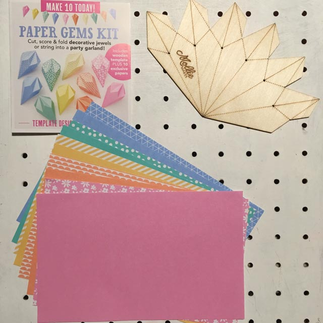 Mollie Makes Paper Gems Kit contents on a white peg board