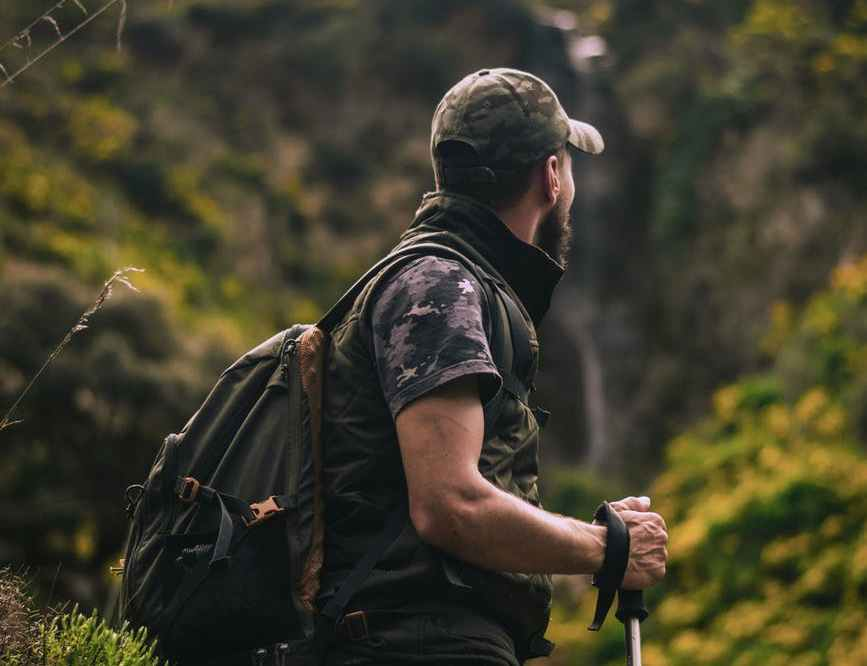 man wearing cap and crew neck shirt standing in the middle of forest
