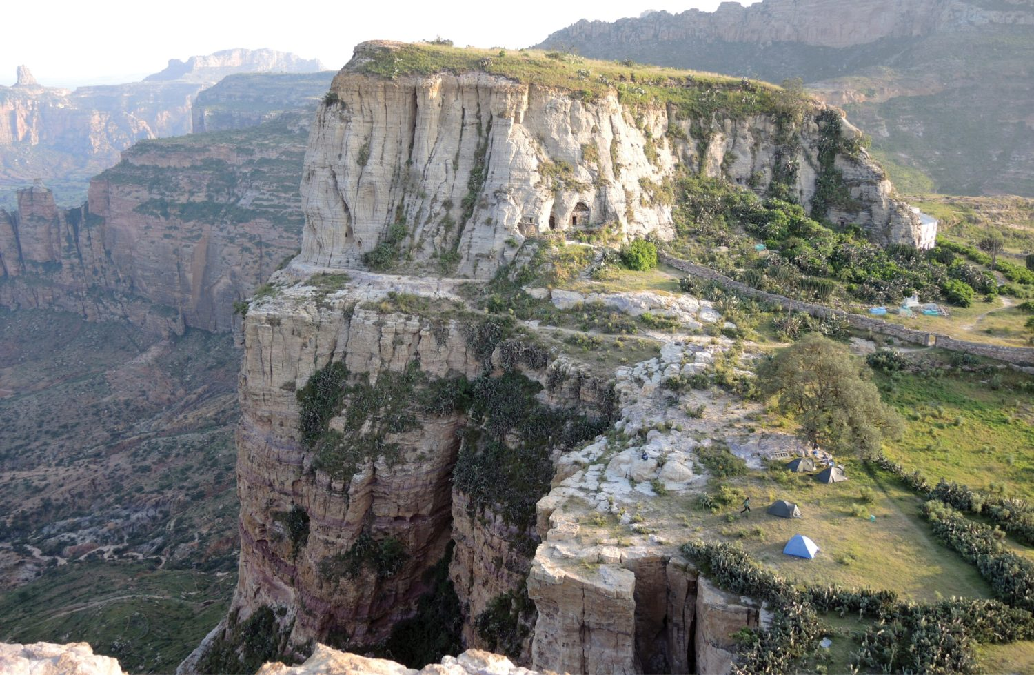 Above A large number of churches are built into the cliffs in the northern Ethiopian province of Tigray. Here we look down over the site of the hermit cave church of Daniel Qorqor and its larger neighbour, the church of Maryam Qorqor. The modern-built facade of the church is visible just at the right edge of the cliff.