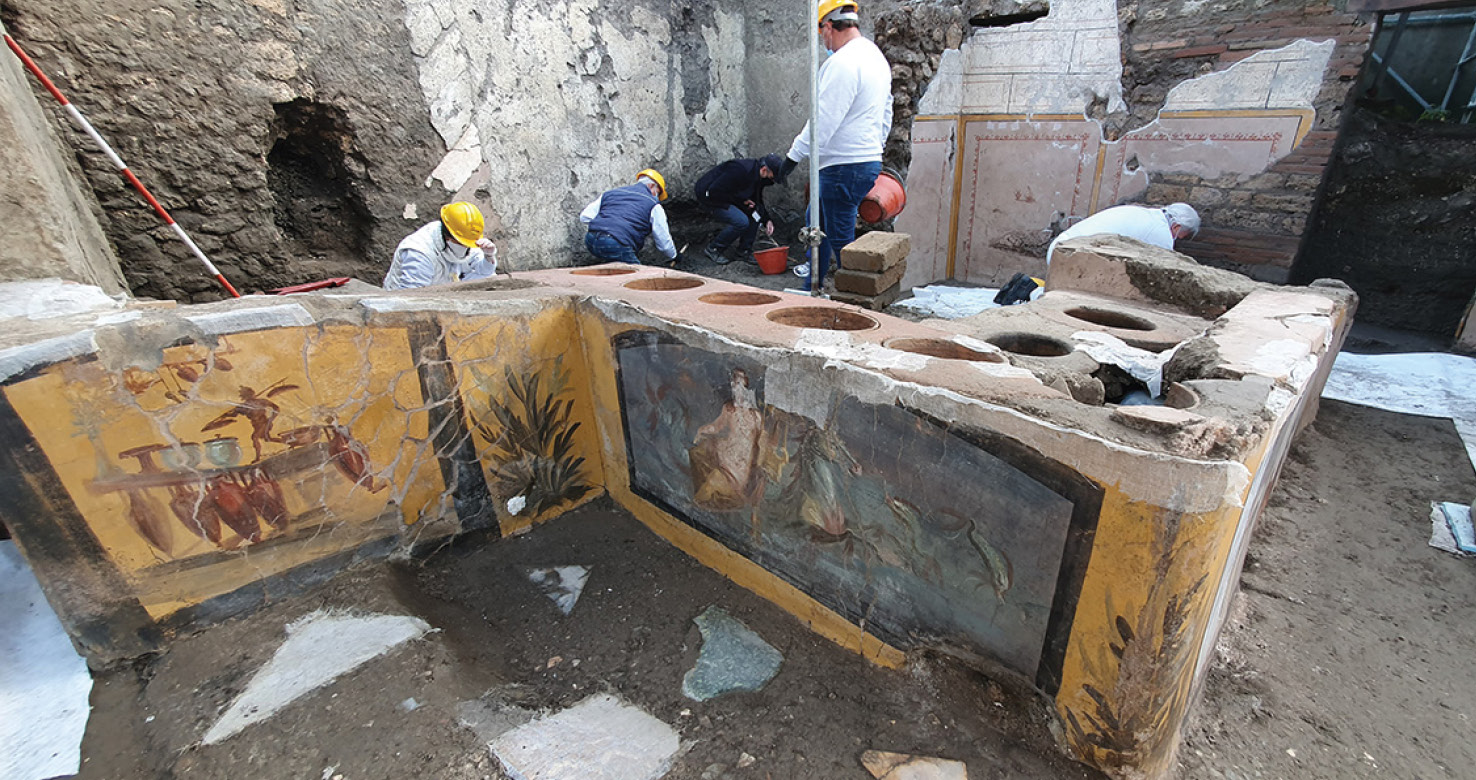 Below Other paintings on the counter include a Nereid (in the centre) discovered in 2019, and a depiction of a thermopolium (on the left).