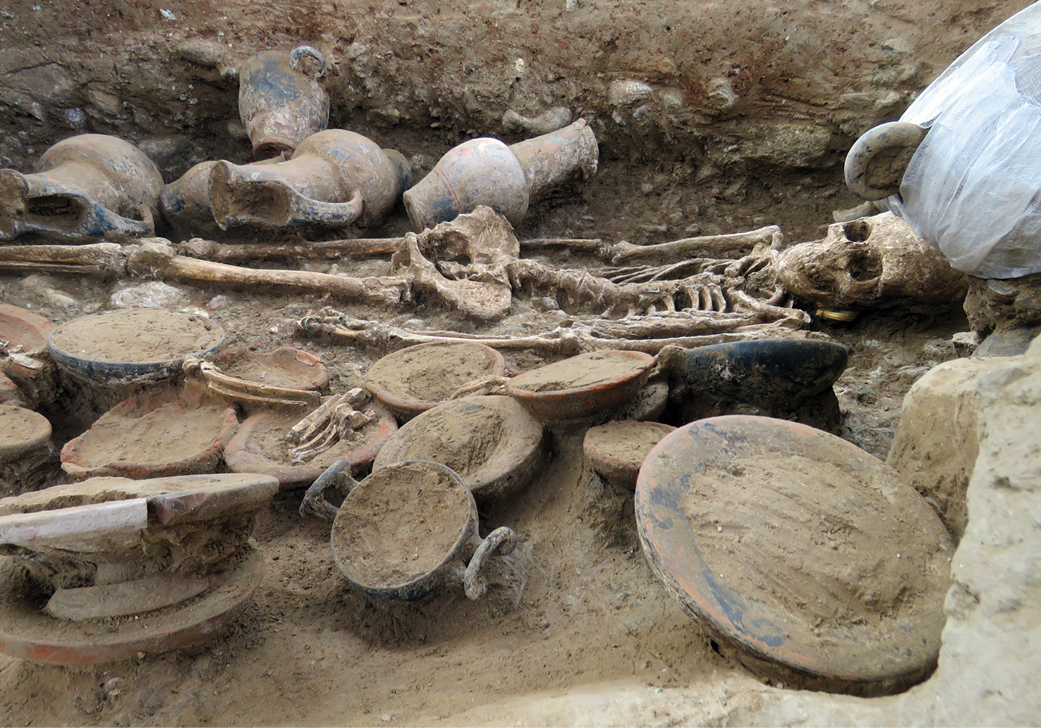left A view of the burial, as seen from the entrance to the burial chamber via the corridor. In the foreground, there are goblets and cups, as well as animal remains. Beyond lie the remains of the woman buried in the chamber, and then the painted jugs.