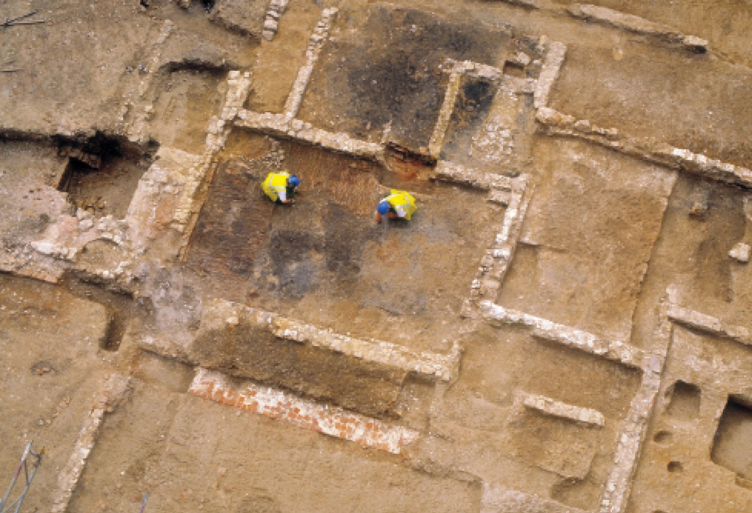 above The first excavation of an English medieval pharmacy: this overhead view (north is to the bottom) shows the large tile-built hearth within the timber-framed building. The original canons' infirmary is to the right, while a later phase of the infirmary layout, partially excavated, can be seen at the top of the photo.