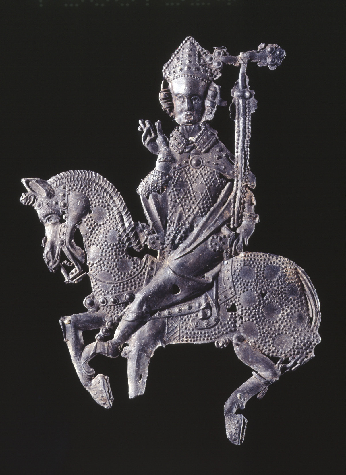 ABOVE Pilgrim badge, showing Becket on horseback returning from exile, 14th century. Lead alloy. Size: 9.3 x 7.7cm