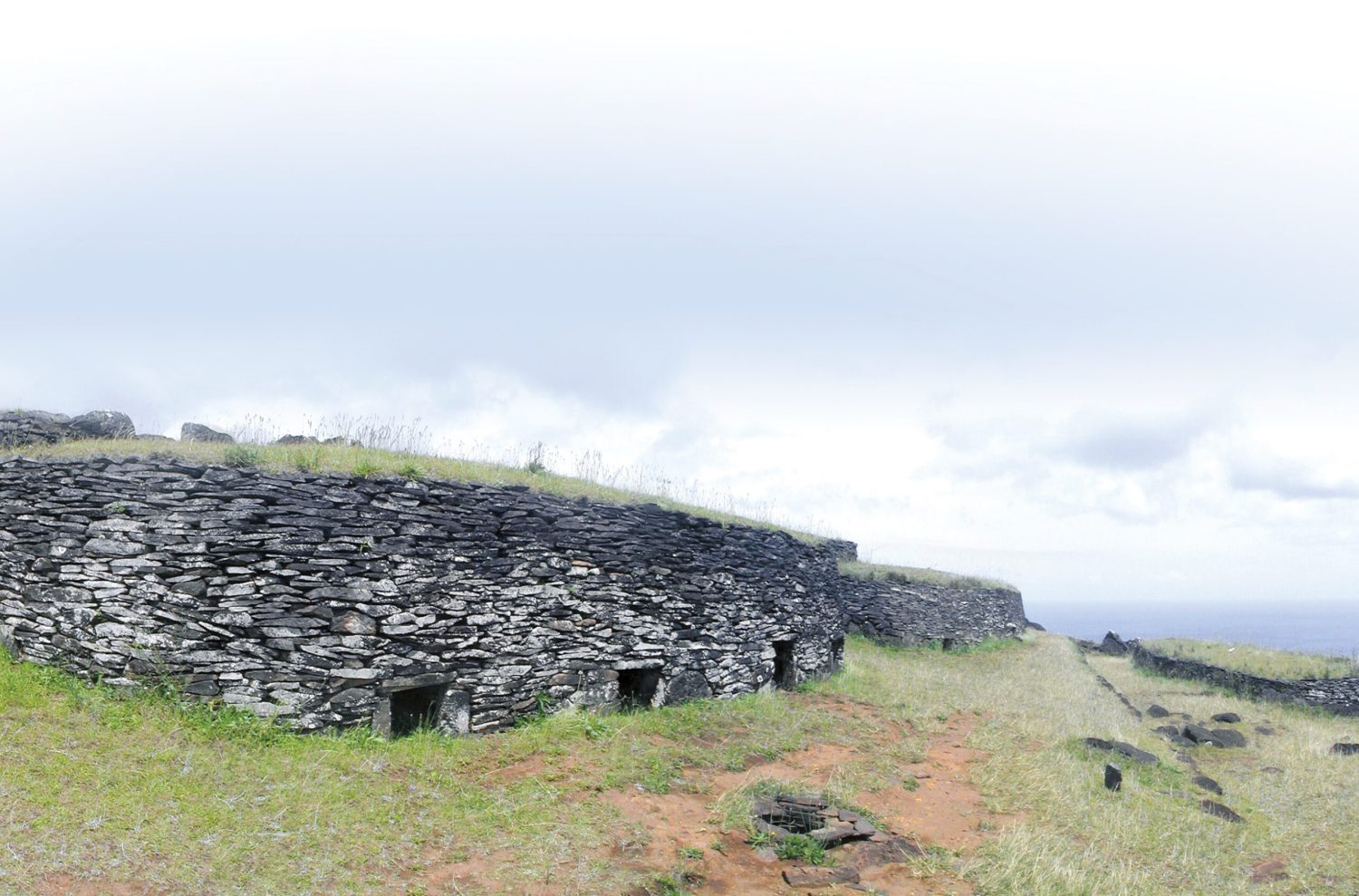 below Stone houses of Orongo village, constructed of dry-laid basalt slabs. The foreground four-entrance house, called Taura Renga, once sheltered the moai called Hoa Hakananai'a.