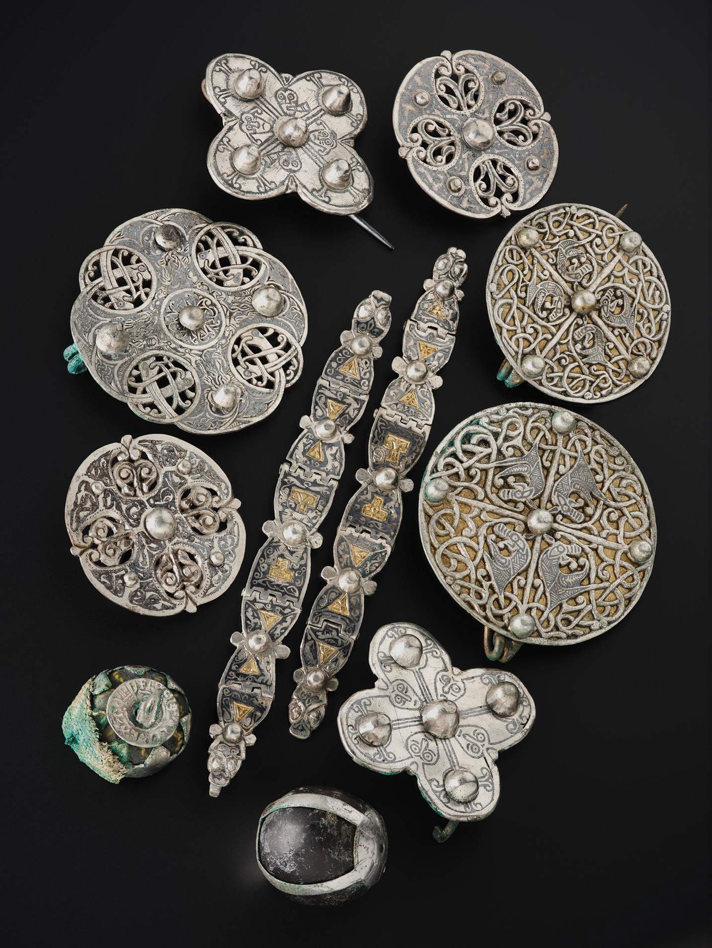 RIGHT A lidded vessel contained a host of unusual objects, including these Anglo-Saxon brooches and straps, as well as unusual pendants of glass and rock crystal. Anglo-Saxon metalwork is rarely found in Scotland, and many of the designs within the vessel are unique.