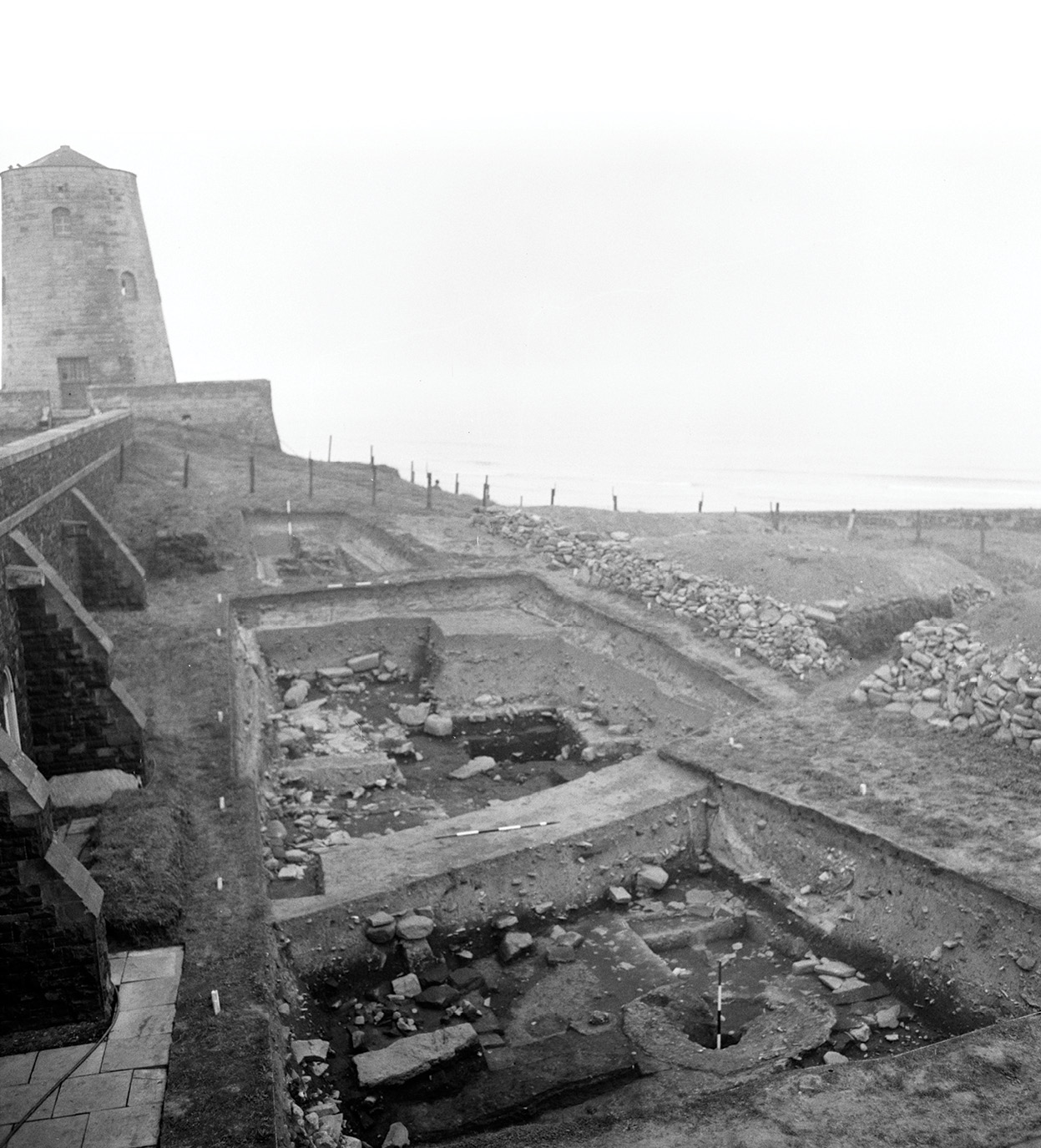 Below Hope-Taylor photograph from the early 1970s of Cutting A, main area divided by a baulk, and Cutting B, the small trench in the background. The mortar mixer is visible towards the bottom of the photograph.