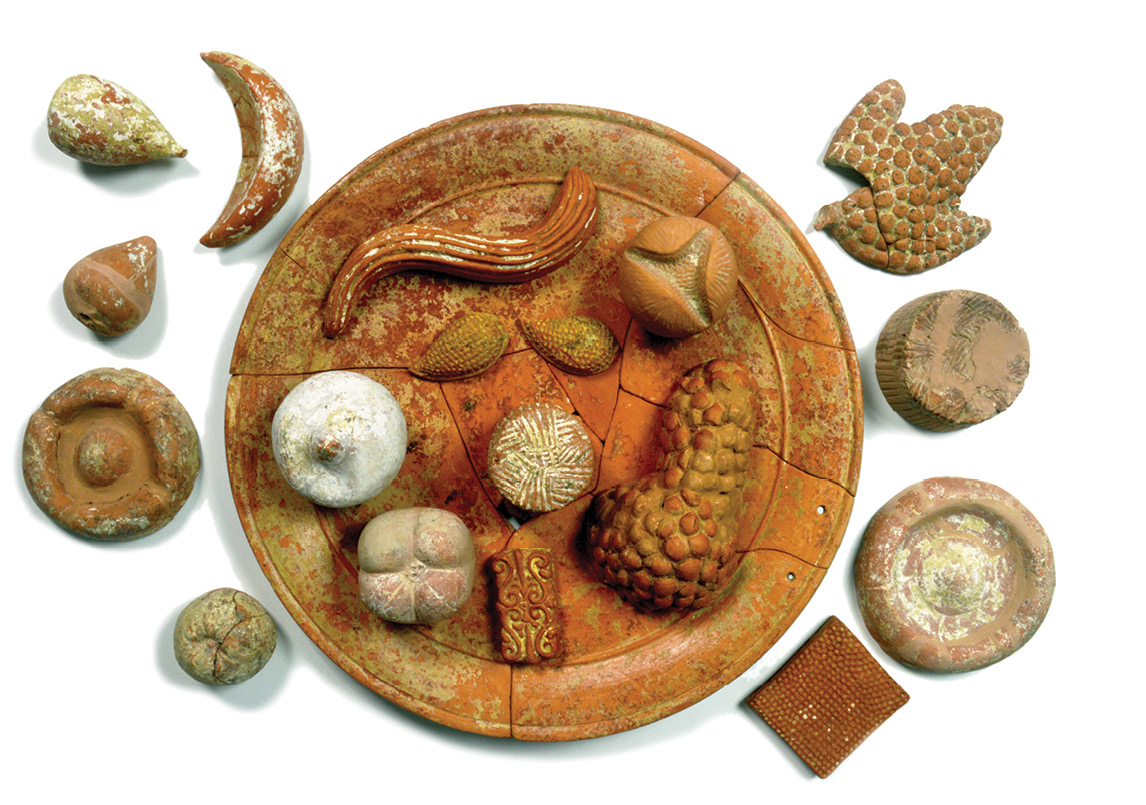 below Food played an important part in funerary customs in ancient Italy. This plate of terracotta votive food (including open and closed pomegranates, grapes, figs, honeycombs, cheeses, and breads) was found in a 360 BC tomb in Paestum.