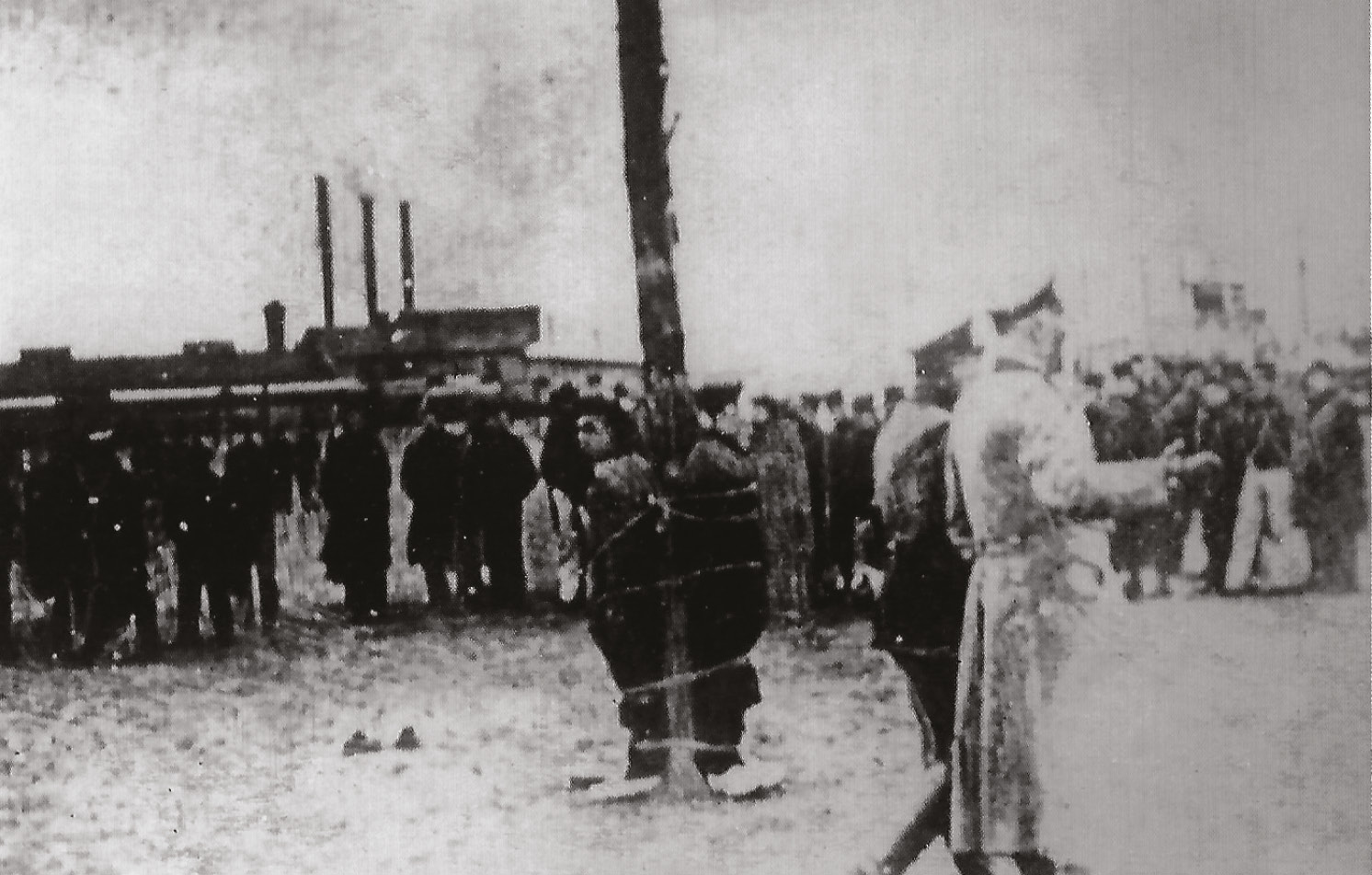 RIGHT This grainy image shows British soldiers tied to a post in a German POW camp, one of many violations of the Hague Conventions.